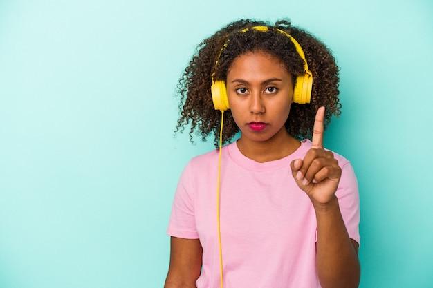 指でナンバーワンを示す青い背景で隔離の音楽を聞いている若いアフリカ系アメリカ人の女性。