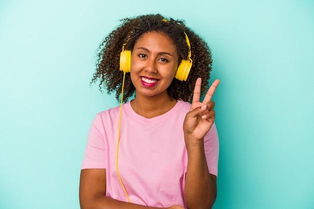 指で2番目を示す青い背景で隔離の音楽を聞いている若いアフリカ系アメリカ人の女性。