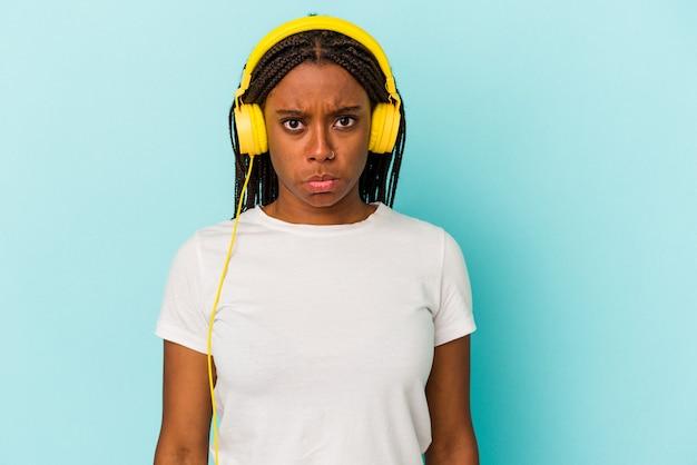 파란색 배경에 격리된 음악을 듣고 있는 젊은 아프리카계 미국인 여성은 어깨를 으쓱하고 혼란스러운 눈을 뜨고 있습니다.