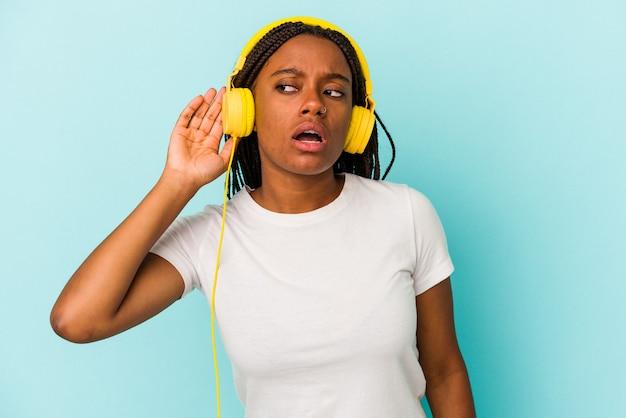ゴシップを聴こうとしている青い背景で隔離の音楽を聞いている若いアフリカ系アメリカ人の女性。