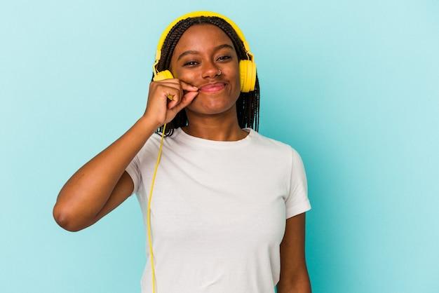 秘密を保持している唇に指で青い背景に分離された音楽を聞いている若いアフリカ系アメリカ人の女性。