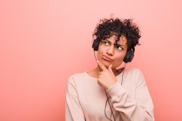 疑わしいと懐疑的な表現で横向きに音楽を聴いている若いアフリカ系アメリカ人の女性。