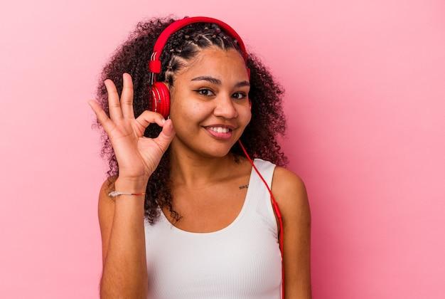 쾌활하고 자신감이 확인 제스처를 보여주는 분홍색 배경에 고립 된 헤드폰으로 음악을 듣고 젊은 아프리카 계 미국인 여자.