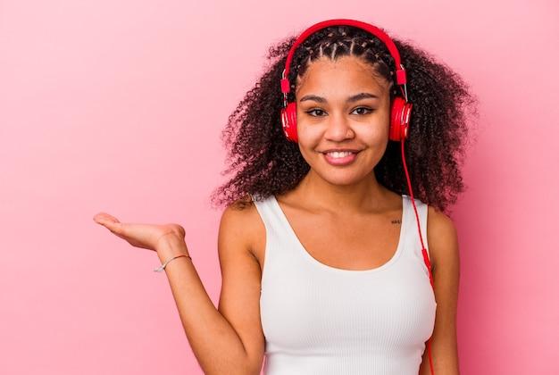 Молодая афро-американская женщина слушает музыку с наушниками, изолированными на розовом фоне, показывая пространство копии на ладони и держа другую руку на талии.