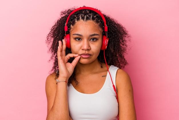 비밀을 유지하는 입술에 손가락으로 분홍색 배경에 고립 된 헤드폰으로 음악을 듣고 젊은 아프리카 계 미국인 여자.