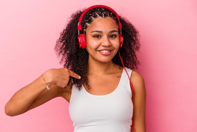誇りと自信を持って、シャツのコピースペースを手で指しているピンクの壁の人に分離されたヘッドフォンで音楽を聴いている若いアフリカ系アメリカ人の女性
