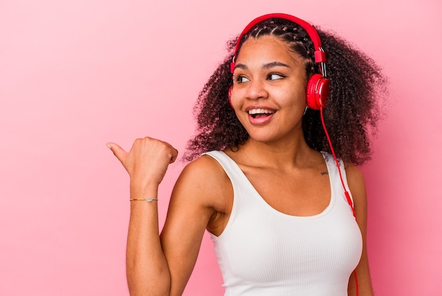 엄지 손가락으로 분홍색 벽 점에 고립 된 헤드폰으로 음악을 듣고 웃고 평온한 젊은 아프리카 계 미국인 여자