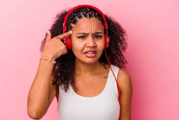 집게 손가락으로 실망 제스처를 보여주는 분홍색 벽에 고립 된 헤드폰으로 음악을 듣고 젊은 아프리카 계 미국인 여자