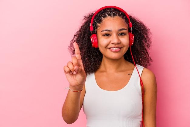 ピンクの壁に分離されたヘッドフォンで音楽を聴いている若いアフリカ系アメリカ人女性は、指でナンバーワンを示しています。