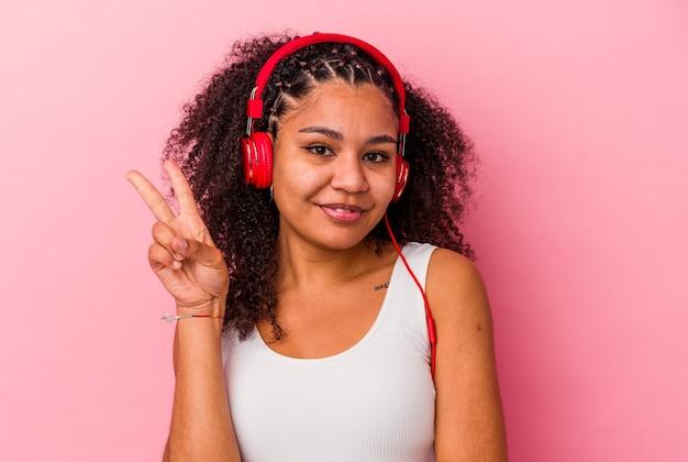 손가락으로 2 번을 보여주는 분홍색 벽에 고립 된 헤드폰으로 음악을 듣고 젊은 아프리카 계 미국인 여자