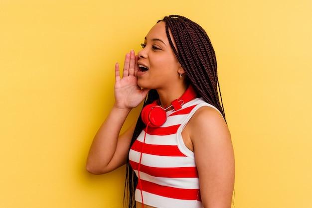 노란색 소리와 열린 된 입 근처 손바닥을 들고에 고립 된 헤드폰으로 음악을 듣고 젊은 아프리카 계 미국인 여자.