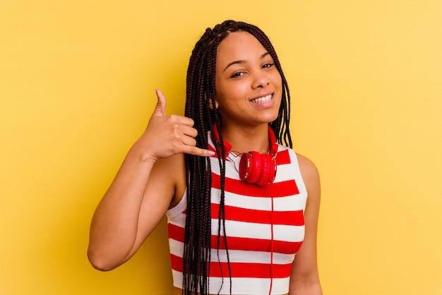 손가락으로 휴대 전화 제스처를 보여주는 노란색 벽에 고립 된 헤드폰으로 음악을 듣고 젊은 아프리카 계 미국인 여자