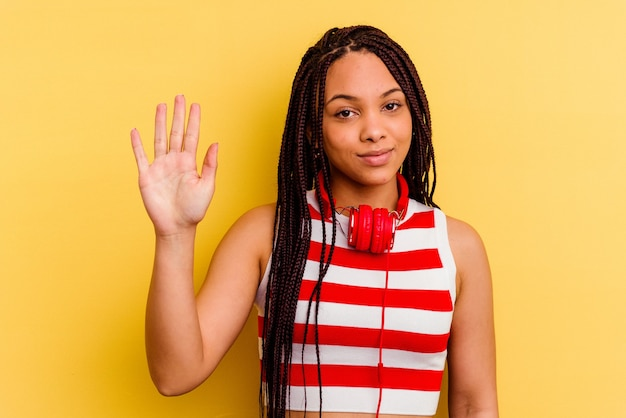 노란색 벽에 고립 된 헤드폰으로 음악을 듣고 젊은 아프리카 계 미국인 여자 손가락으로 명랑 보여주는 번호 5 미소