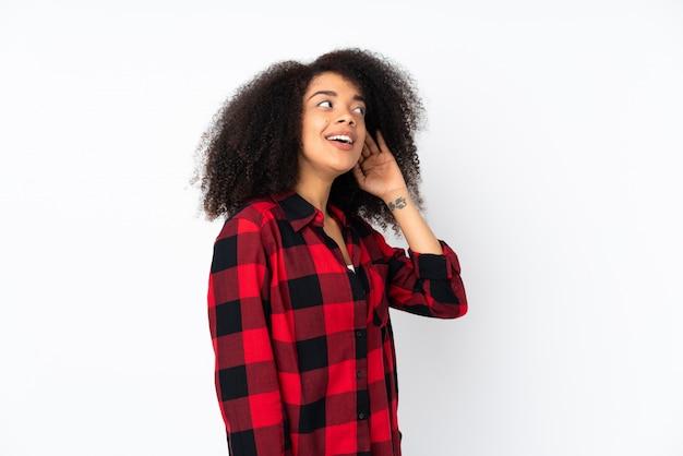 耳に手を置くことによって何かを聞いて若いアフリカ系アメリカ人女性