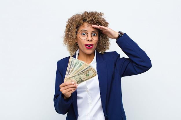 Молодая афроамериканская женщина, выглядящая счастливой, удивленной и удивленной, улыбающейся и понимающей удивительные и невероятные хорошие новости с банкнотами евро