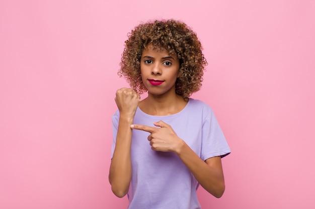 Молодая афро-американская женщина выглядит нетерпеливой и сердитой, указывая на часы, прося пунктуальности, хочет быть вовремя у розовой стены