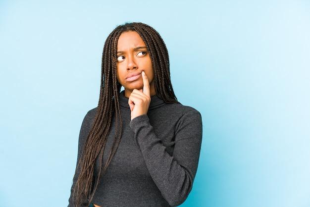 Молодая афро-американская женщина смотрит в сторону с сомнительным и скептическим выражением лица.