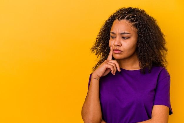 의심스럽고 회의적인 표정으로 옆으로 찾고 젊은 아프리카 계 미국인 여자.
