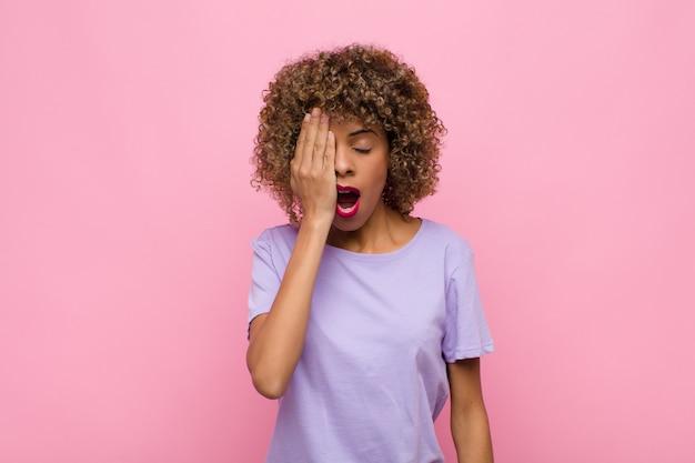 Молодая афроамериканка выглядит сонной, скучающей и зевая, с головной болью и одной рукой, держащей половину лица на розовой стене