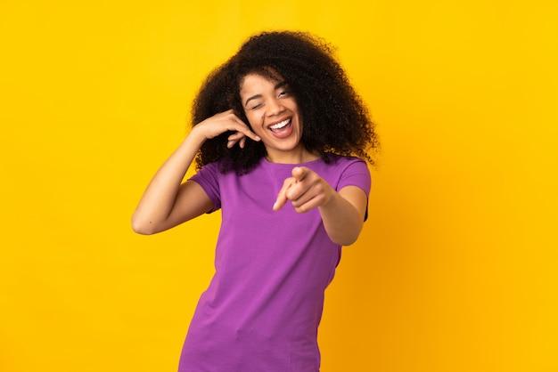 電話のジェスチャーを作ると前方を向く若いアフリカ系アメリカ人女性