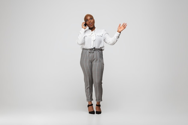 Young african-american woman in office attire on gray
