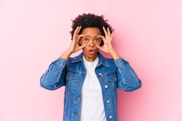 Молодая афро-американская женщина на розовом backgroound изолировала, держа глаза открытыми, чтобы найти возможность успеха.
