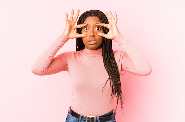 Молодая афро-американская женщина на розовой стене держа глаза открытыми