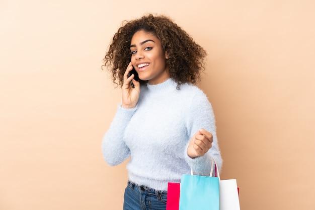 Молодая афро-американская женщина на бежевой стене держа хозяйственные сумки и вызывая друга с ее сотовым телефоном
