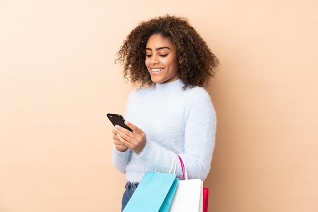 Молодая афро-американская женщина на бежевой стене держа хозяйственные сумки и писать сообщение с ее сотовым телефоном другу