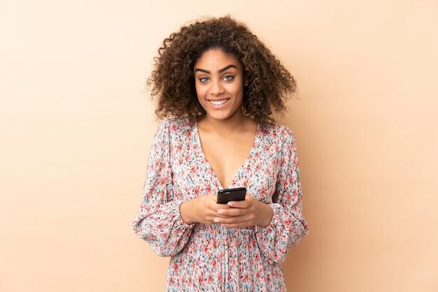 Молодая афроамериканка на бежевой стене, отправив сообщение с мобильного телефона