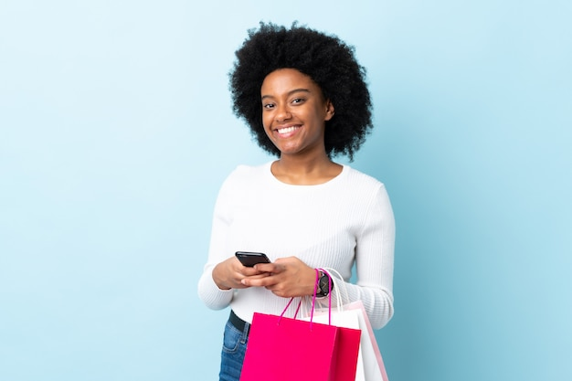 Молодая афро-американская женщина на голубой стене держа хозяйственные сумки и писать сообщение с ее сотовым телефоном к другу