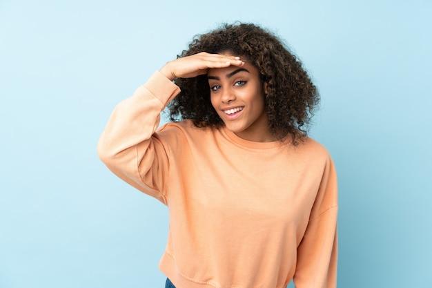 何かを見て手で遠く離れている青い壁の若いアフリカ系アメリカ人女性