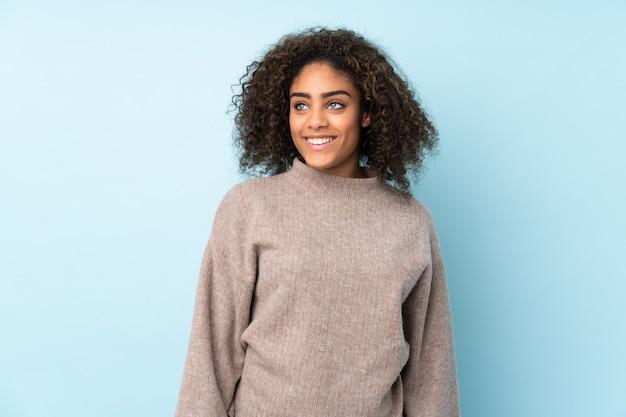 Молодая афро-американская женщина на голубой стене думая идея пока смотрящ вверх
