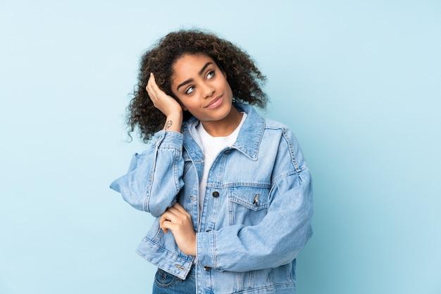 Молодая афро-американская женщина на голубой стене думая идея