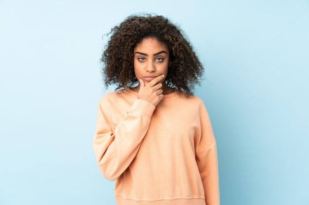 Молодая афро-американская женщина на голубой стене думая