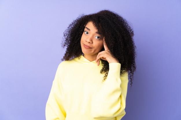 Молодая афро-американская женщина на фиолетовой стене думая идея