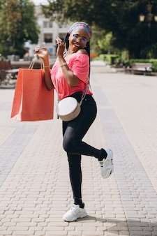買い物袋が付いている通りの若いアフリカ系アメリカ人女性