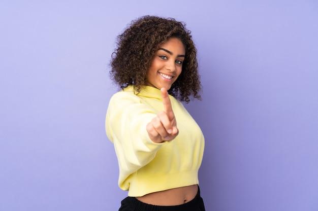 壁を示すと指を持ち上げる若いアフリカ系アメリカ人女性 Premium写真