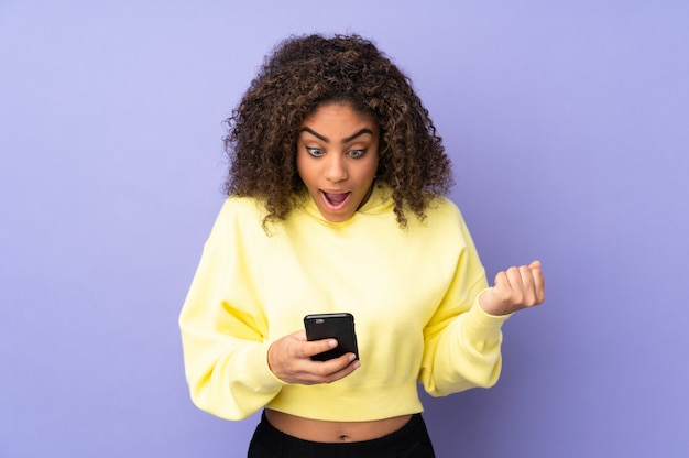 Молодая женщина афроамериканцев на стене удивлен и отправив сообщение