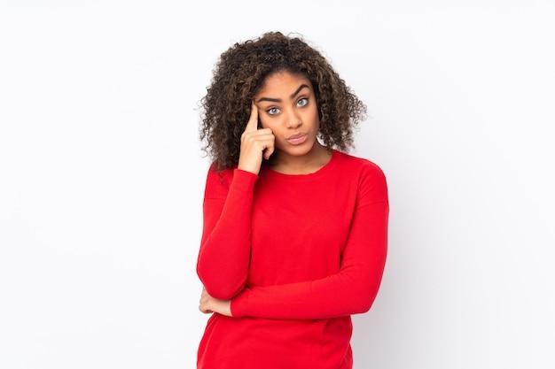Молодая афро-американская женщина на стене думая идея
