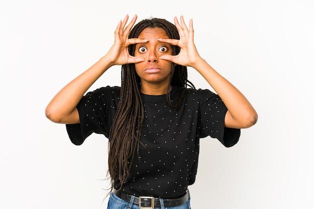 Молодая афро-американская женщина на белом держит глаза открытыми, чтобы найти возможность успеха.