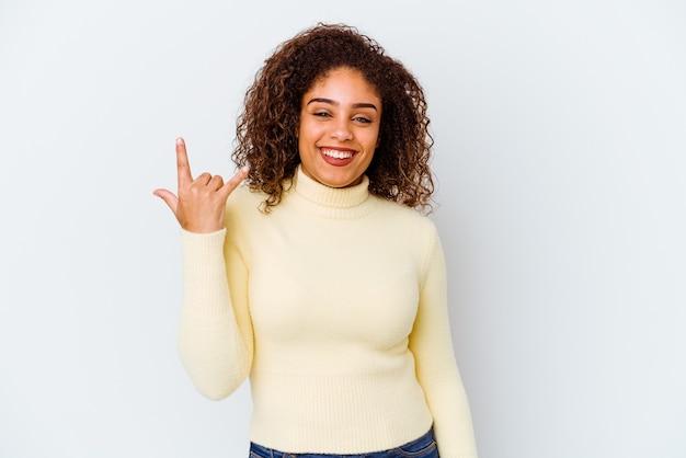 손가락으로 바위 제스처를 보여주는 흰색에 젊은 아프리카 계 미국인 여자