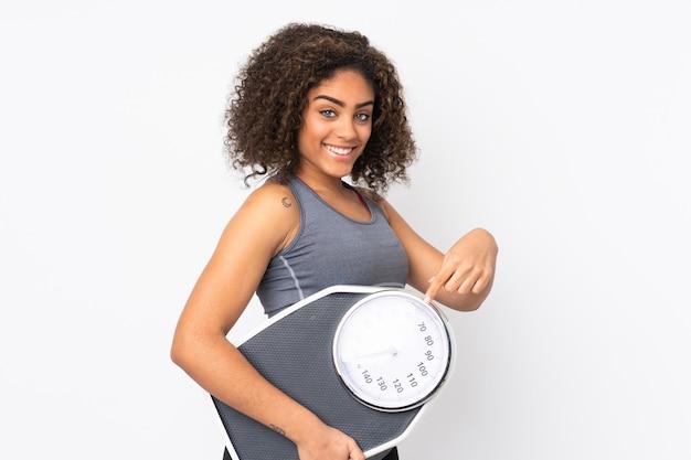 무게 기계를 들고 그것을 가리키는 흰 벽에 젊은 아프리카 계 미국인 여자