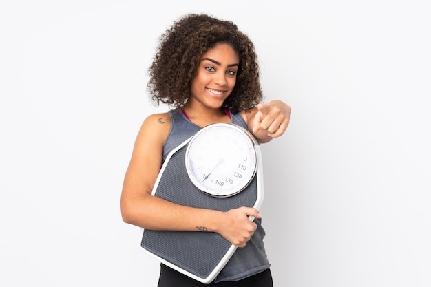 무게 기계를 잡고 앞을 가리키는 흰 벽에 젊은 아프리카 계 미국인 여자