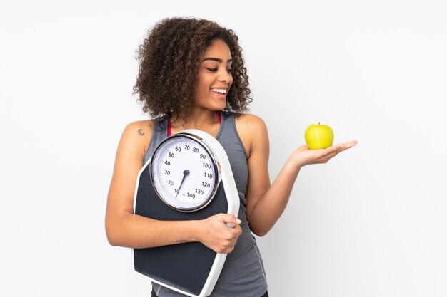 사과 보면서 무게 기계를 들고 흰 벽에 젊은 아프리카 계 미국인 여자