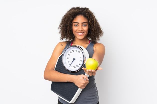 Молодая афро-американская женщина на белой стене держа веся машину и предлагая яблоко