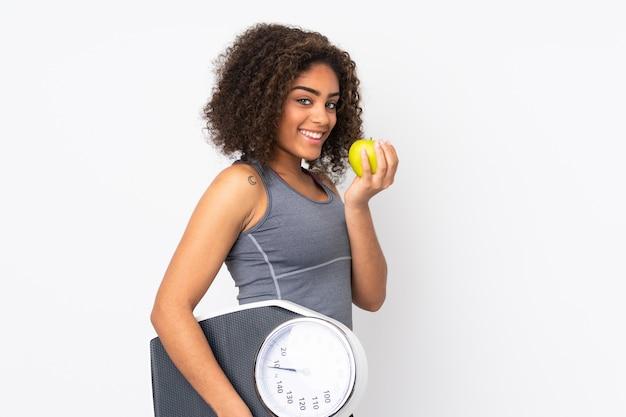 Молодая афро-американская женщина на белой стене с весами и с яблоком