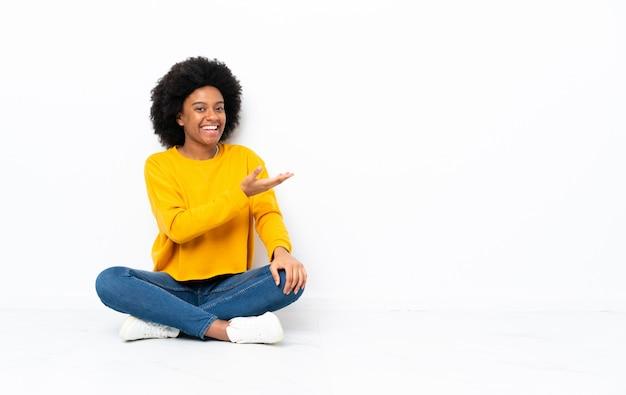 Молодая афро-американская женщина над изолированной предпосылкой