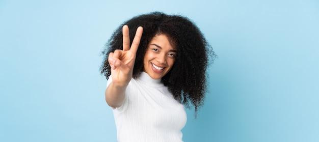 孤立した笑顔と勝利の兆候を示す上の若いアフリカ系アメリカ人女性