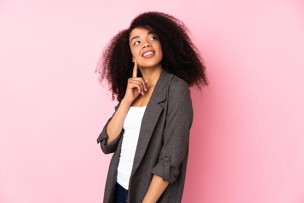 Молодая афро-американская женщина над стеной думая идея пока смотрящ вверх